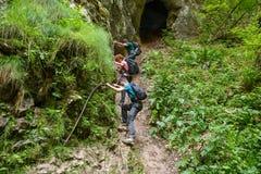 Familia de caminantes que se aferran a un cable de la seguridad Imagen de archivo