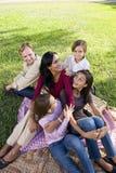 Familia de cinco que tienen comida campestre en parque Imágenes de archivo libres de regalías