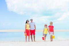 Familia de cuatro miembros el las vacaciones de la playa que se divierten mucho Imagen de archivo