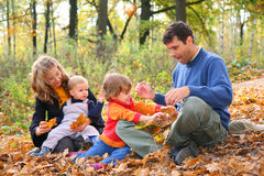 Familia de cuatro miembros en bosque en otoño Foto de archivo