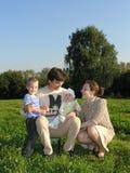 Familia de cuatro miembros en el cielo azul de madera de la hierba Foto de archivo libre de regalías