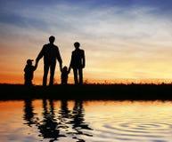 Familia de cuatro miembros en el cielo de la puesta del sol imagenes de archivo
