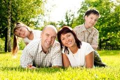 Familia de cuatro miembros en hierba Foto de archivo libre de regalías