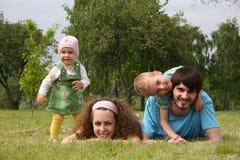 Familia de cuatro miembros en hierba Imagen de archivo libre de regalías