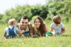 Familia de cuatro miembros en hierba en el parque Fotografía de archivo