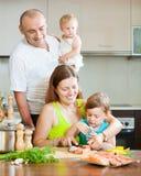 Familia de cuatro miembros en la cocina que prepara los mariscos Imagen de archivo libre de regalías