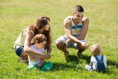 Familia de cuatro miembros en parque soleado Imagen de archivo