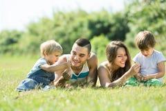 Familia de cuatro miembros en parque soleado Imágenes de archivo libres de regalías