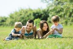 Familia de cuatro miembros en parque soleado Imagenes de archivo