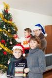 Familia de cuatro miembros feliz con el árbol de navidad Fotos de archivo libres de regalías