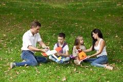 Familia de cuatro miembros feliz, descansando en el parque del otoño Imágenes de archivo libres de regalías