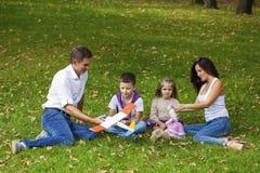 Familia de cuatro miembros feliz, descansando en el parque del otoño Imagenes de archivo
