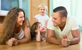 Familia de cuatro miembros feliz en casa imagen de archivo libre de regalías