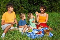 Familia de cuatro miembros feliz en comida campestre en jardín Imágenes de archivo libres de regalías