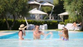 Familia de cuatro miembros feliz en piscina del aire libre metrajes