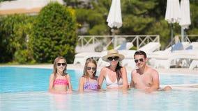 Familia de cuatro miembros feliz en piscina del aire libre almacen de metraje de vídeo