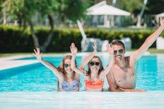 Familia de cuatro miembros feliz en piscina del aire libre foto de archivo