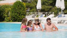Familia de cuatro miembros feliz en piscina del aire libre almacen de video