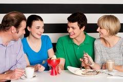 Familia de cuatro miembros feliz en restaurante imagen de archivo libre de regalías