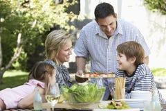 Familia de cuatro miembros feliz que almuerza al aire libre Fotografía de archivo libre de regalías