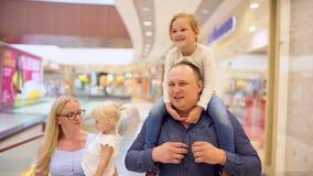 Familia de cuatro miembros feliz que hace compras Familia en alameda Niños en la alameda con los padres Compras de la familia en  almacen de metraje de vídeo