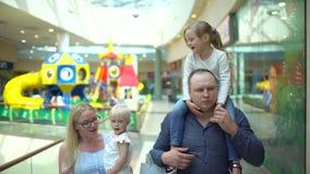Familia de cuatro miembros feliz que hace compras Familia en alameda Niños en la alameda con los padres Compras de la familia en  almacen de video