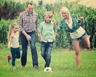 Familia de cuatro miembros feliz que juega a fútbol Imagen de archivo