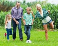 Familia de cuatro miembros feliz que juega a fútbol Foto de archivo libre de regalías