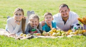 Familia de cuatro miembros feliz que miente en el parque Fotos de archivo libres de regalías