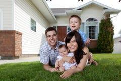 Familia de cuatro miembros feliz que se acuesta en hierba Fotos de archivo