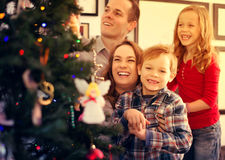 Familia de cuatro miembros feliz que se prepara para la Navidad Fotografía de archivo