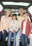 Familia de cuatro miembros feliz que se sienta en tronco de coche Imágenes de archivo libres de regalías