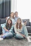 Familia de cuatro miembros feliz que ve la TV junto en casa Imágenes de archivo libres de regalías