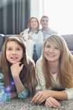 Familia de cuatro miembros feliz que ve la TV junto en casa Fotografía de archivo