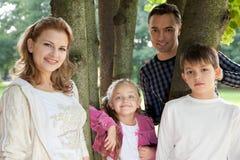 Familia de cuatro miembros feliz sonriente al aire libre Imagen de archivo