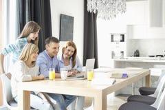 Familia de cuatro miembros feliz usando el ordenador portátil en casa Imagen de archivo