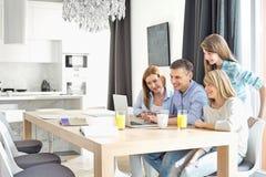 Familia de cuatro miembros feliz usando el ordenador portátil en casa Fotos de archivo libres de regalías
