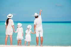 Familia de cuatro miembros joven en blanco en la playa tropical PArent con dos niños que miran el mar Foto de archivo