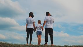 Familia de cuatro miembros joven feliz que se divierte en el top de una colina en un fondo de nubes Familia de cuatro miembros qu almacen de video