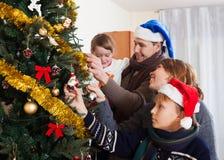 Familia de cuatro miembros que adorna el árbol de navidad Imagen de archivo libre de regalías