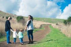 Familia de cuatro miembros que camina junto abajo de la trayectoria en el holdin del parque Imágenes de archivo libres de regalías