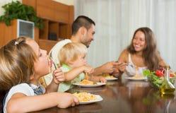 Familia de cuatro miembros que come los espaguetis Foto de archivo libre de regalías