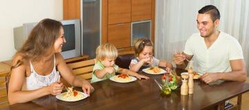 Familia de cuatro miembros que come los espaguetis Imagen de archivo