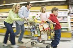 Familia de cuatro miembros que corre con la carretilla llena de las compras Imágenes de archivo libres de regalías