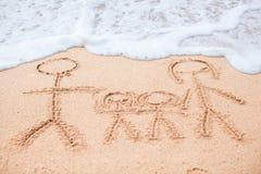 Familia de cuatro miembros que dibuja en la playa Imágenes de archivo libres de regalías