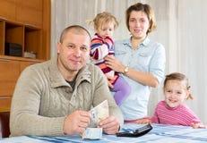 Familia de cuatro miembros que planea el presupuesto Imagenes de archivo