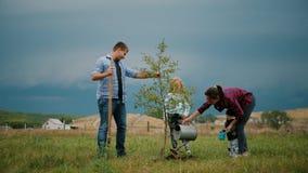 Familia de cuatro miembros que planta un nuevo árbol en su jardín El concepto es plantar los árboles, familia amistosa almacen de metraje de vídeo