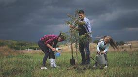 Familia de cuatro miembros que planta un nuevo árbol en su jardín El concepto es plantar los árboles, familia amistosa almacen de video