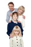 Familia de cuatro miembros que presenta en fila imágenes de archivo libres de regalías