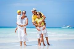 Familia de cuatro miembros que se divierte en la playa Imágenes de archivo libres de regalías